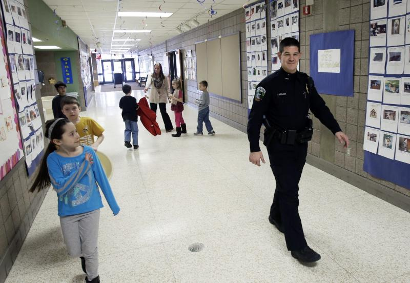 FILE - In this Feb. 21, 2013 file photo, a young girl waves at police officer Jeff Strack as he walks the hallway of Jordan Elementary School in Jordan, Minn., a small town that decided to place satellite police offices in its public schools. Gun rights supporters in Jordan had made a push to arm school personnel after the Connecticut school shooting four months ago, but those proposals have stalled in many other states. (AP Photo/Jim Mone, File)