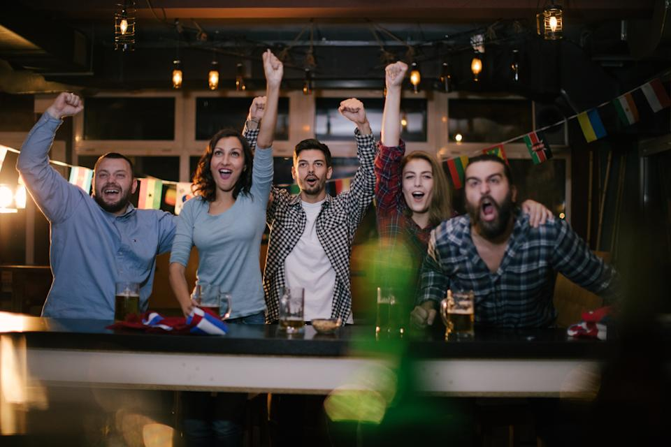 Group of young people, sitting in a pub all together, watching a sports game.