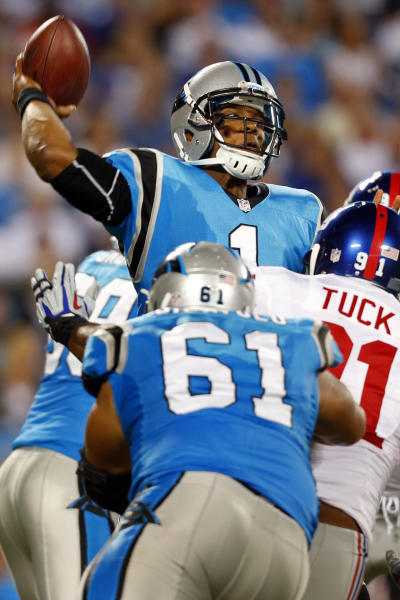 Carolina Panthers quarterback Cam Newton (1) throws a pass under pressure from New York Giants defensive end Justin Tuck (91) during the second quarter of an NFL football game in Charlotte, N.C., Thursday, Sept. 20, 2012. (AP Photo/Bob Leverone)