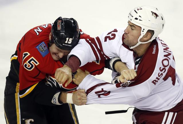 Phoenix Coyotes' Paul Bissonnette, right, fights with Calgary Flames' Tim Jackman during the third period of an NHL preseason hockey game, Wednesday, Sept. 25, 2013, in Calgary, Alberta. The Coyotes won 3-2. (AP Photo/The Canadian Press, Jeff McIntosh)