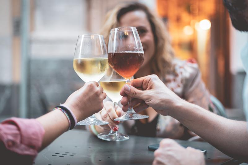A group of friends holding the glasses of wine making a toast in an outdoor bar.