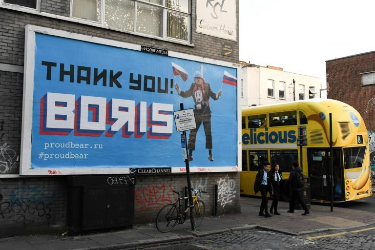 "A Brexit-themed billboard depicting Britain's former foreign secretary Boris Johnson waving Russian national flags reading ""Thank you Boris"""