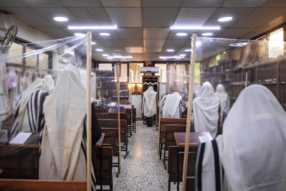 Ultra-Orthodox Jews praying in a synagogue separated by plastic partitions, follow new government measures to help stop the spread of the coronavirus, in Bnei Brak, Israel, Friday, Sept 18, 2020. Israel is set to go back into a three-week lockdown later Friday to try to contain a coronavirus outbreak that has steadily worsened for months as its government has been plagued by indecision and infighting. The closures coincide with the Jewish High Holidays, when people typically visit their families and gather for large prayer services. (AP Photo/Oded Balilty)