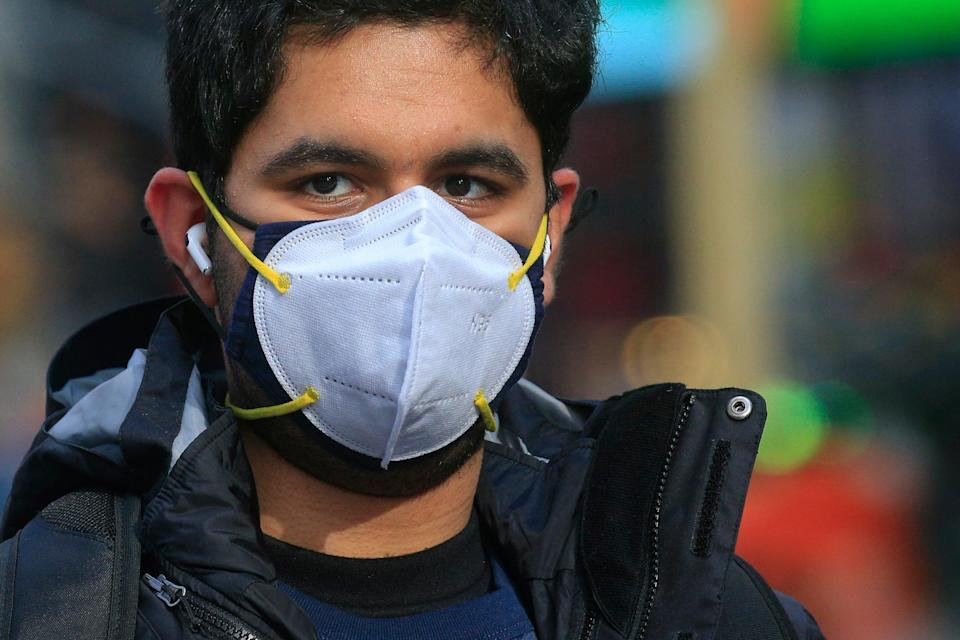 A man wears a double mask as he visits Times Square in New York (AFP via Getty Images)