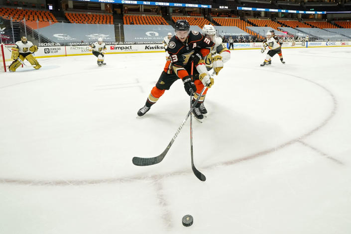 Anaheim Ducks right wing Jakob Silfverberg, left, and Vegas Golden Knights center Nicolas Roy battle for the puck during the second period of an NHL hockey game Saturday, Feb. 27, 2021, in Anaheim, Calif. (AP Photo/Mark J. Terrill)
