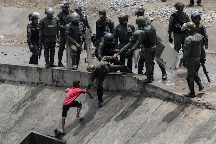 Members of the Boliviarian Guard prevent a child from collecting water from a broken pipe flowing into a sewage canal at the Guaire river in Caracas on March 11, 2019 (AFP Photo/Cristian HERNANDEZ)