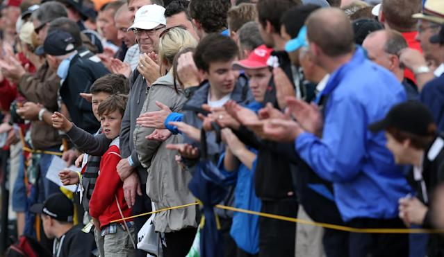 Young golf fans applaud as they wait for Rory McIlroy of Northern Ireland to pass by on the 17th hole during the third day of the British Open Golf championship at the Royal Liverpool golf club, Hoylake, England, Saturday July 19, 2014. (AP Photo/Jon Super)