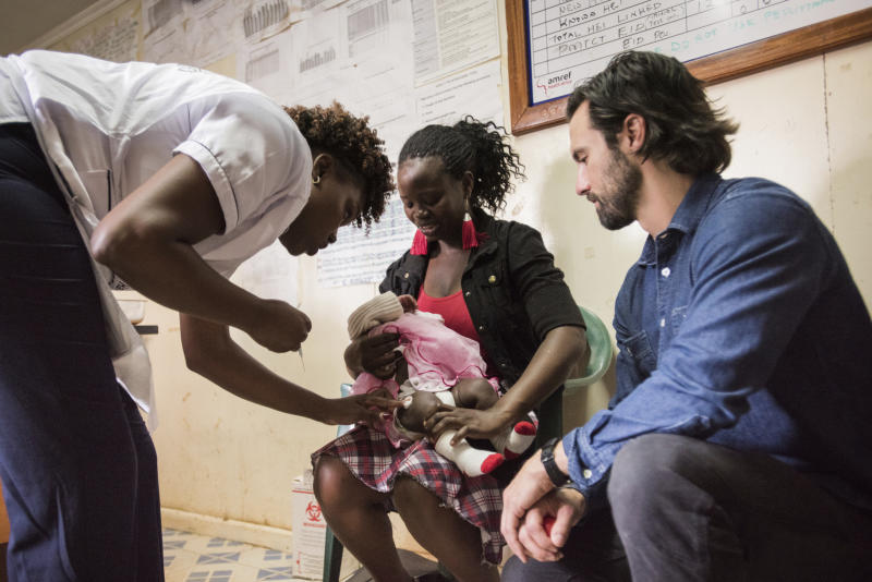 "This image released by NBC shows actor Milo Ventimiglia visiting the vaccination clinic at Kibera AMREF Health Centre in Nairobi, Kenya. Ventimiglia, star of the series ""This Is Us,"" traveled to the outskirts of Nairobi, Kenya, and saw programs supported by the campaign providing health care, education and more. Video of his trip is included in NBC's two-hour Red Nose Day special airing Thursday with host Terry Crews. (Mia Collis/NBC via AP)"