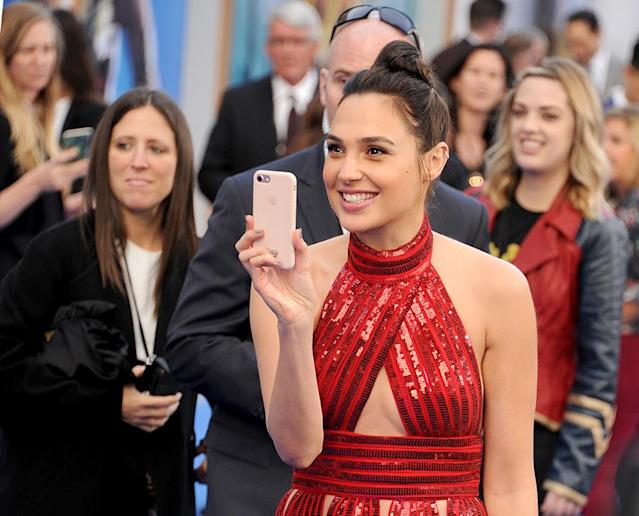 <p>Gadot snaps photos on the red carpet. (Photo: Gregg DeGuire/WireImage) </p>