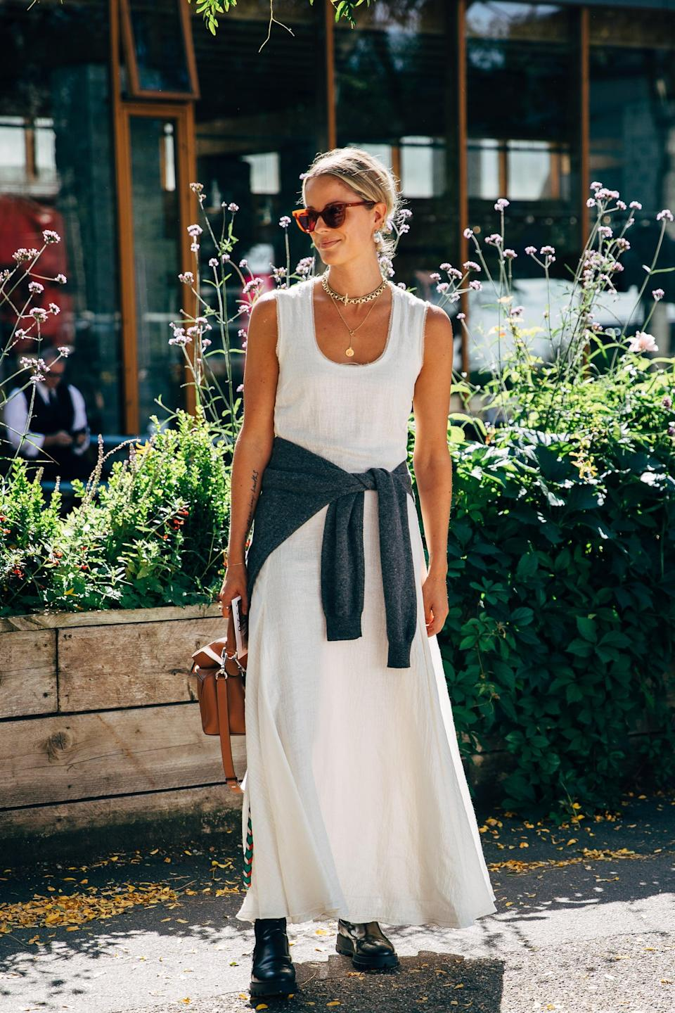 <p>A sleeveless maxi gets grounded with a pair of boots and an added layer. </p>