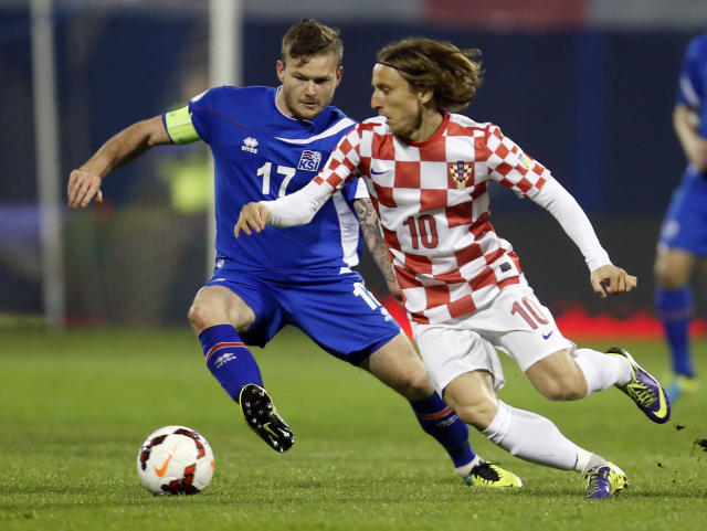 FILE - In this Nov. 19, 2013, file photo, Iceland's Aron Gunnarsson, left, is challenged by Croatia's Luka Modric during their World Cup qualifying playoff second leg soccer match in Zagreb, Croatia. (AP Photo/Darko Bandic, File)