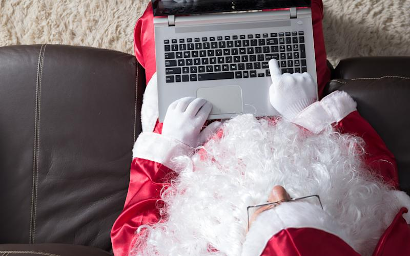 High Angle View Of Person Dressed In Santa Claus Costume Using Laptop While Sitting On Sofa