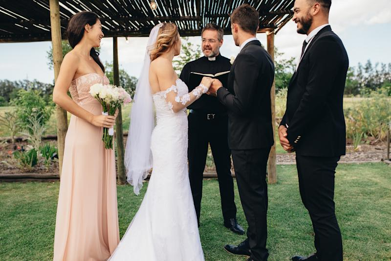 Bride and groom standing in front of priest witness by bridesmaids and best man. Outdoor wedding ceremony of beautiful couple.
