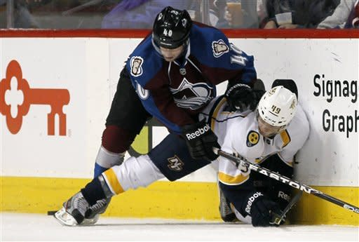 Nashville Predators defenseman Ryan Ellis, right, is pinned to the ice by Colorado Avalanche center Mark Olver as they fight for control of the puck along the boards in the first period of an NHL hockey game in Denver, Saturday, April 7, 2012. (AP Photo/David Zalubowski)