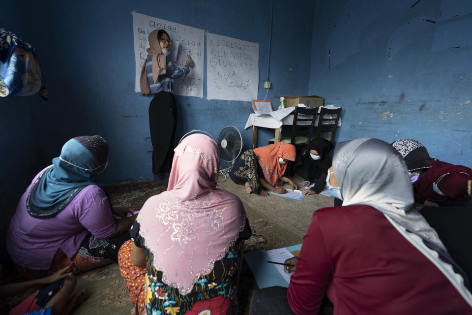 A volunteer teacher gives a basic English lesson to a minority Muslim Rohingya refugees at a slum on the outskirts of Kuala Lumpur, Malaysia, on Oct. 11, 2020. Refugee women in Malaysia, some in their late 50s, are learning to read and write for the first time. The classes outside Kuala Lumpur are offered by the Women for Refugees group, which was formed in September by two law students to help illiterate migrant women integrate into the local community and empower them to be more than just passive wives. (AP Photo/Vincent Thian)