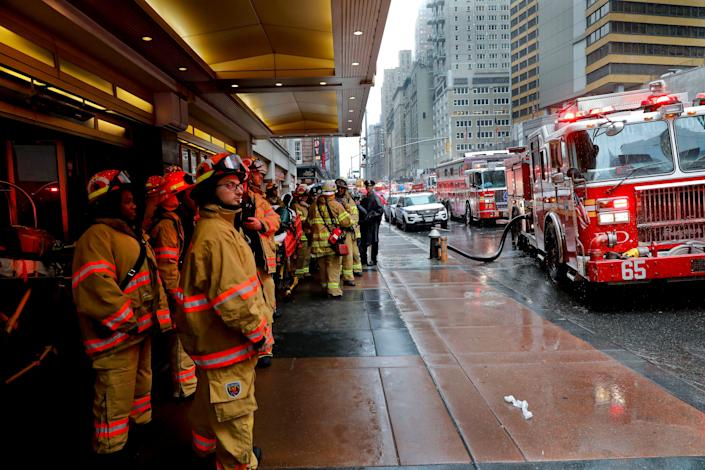 Firefighters respond to the scene where a helicopter crash-landed on the roof of a midtown Manhattan skyscraper.