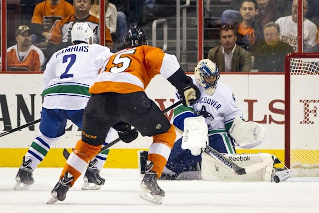 Vancouver Canucks goalie Roberto Luongo, right, makes the initial save as Philadelphia Flyers' Tye McGinn (15) skates in for the rebound before scoring a goal in the first period of a NHL hockey game, Tuesday, Oct. 15, 2013, in Philadelphia. Vancouver's Dan Hamhuis skates in at left. (AP Photo/Chris Szagola)
