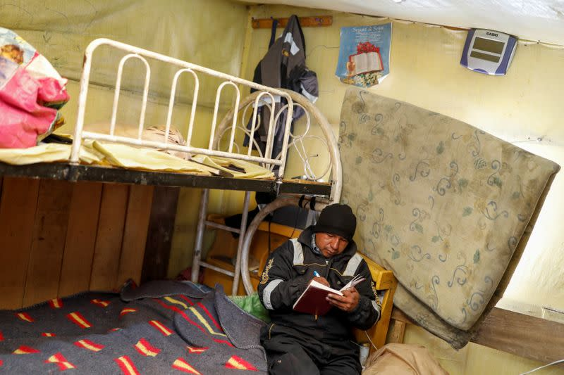 An artisanal gold miner writes in a notebook in his room in La Rinconada, in the Andes