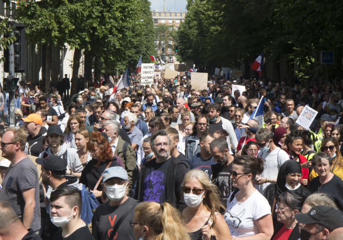 Protesters hold placards during a demonstration against the health pass, in Lille, northern France, Saturday, July 31, 2021. France announced mandatory COVID-19 passes for access to restaurants, bars, shopping malls and many tourist spots, as well as trains and planes, as of July 21. The passes are available to anyone fully vaccinated, recently recovered or who has a recent negative test. (AP Photo/Michel Spingler)