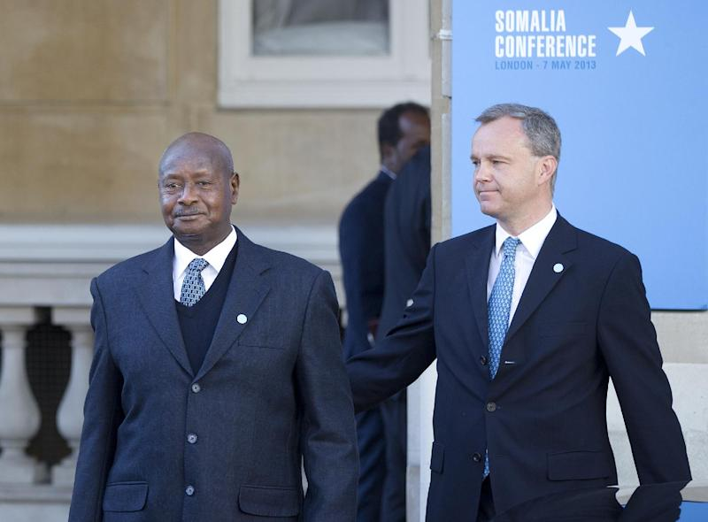 President of Uganda Yoweri Museveni, left, arrives for the Somalia Conference held at Lancaster House in London, Tuesday May 7, 2013. British Prime Minister David Cameron is welcoming Somalia's president and a host of international leaders to London for a conference aimed at securing support for the government in Mogadishu after two decades of conflict. Man at right is unidentified. (AP Photo/Alastair Grant)