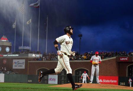 "May 15, 2018; San Francisco, CA, USA; San Francisco Giants first baseman Brandon Belt (9) rounds the bases on a home run against Cincinnati Reds starting pitcher Tyler Mahle (30) as mist fills the sky in recognition of a ""splash hit"" where a ball lands in the water outside the stadium during the fourth inning at AT&T Park. Mandatory Credit: Kelley L Cox-USA TODAY Sports"