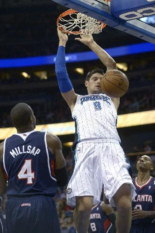 Orlando Magic center Nikola Vucevic (9) dunks the ball over Atlanta Hawks power forward Paul Millsap (4) and point guard Jeff Teague (0) during the first half of an NBA basketball game in Orlando, Fla., Sunday, Dec. 29, 2013.(AP Photo/Phelan M. Ebenhack)