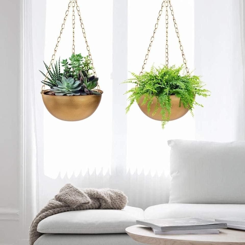 <p>These <span>Sinolodo Gold Hanging Planters, Set of 2</span> ($30) make a statement. These will look stunning against the sunshine.</p>
