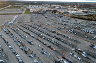 In this aerial photo, a General Motors assembly plant is seen at top right while mid-sized pickup trucks and full-size vans currently produced at the plant are seen in a parking lot outside Wednesday, March 24, 2021, in Wentzville, Mo. As the U.S. economy awakens from its pandemic-induced slumber, a vital cog is in short supply: the computer chips that power our cars and other vehicles, and a vast number of other items we take for granted. Ford, GM and Stellantis have started building vehicles without some computers, putting them in storage with plans to retrofit them later. (AP Photo/Jeff Roberson)