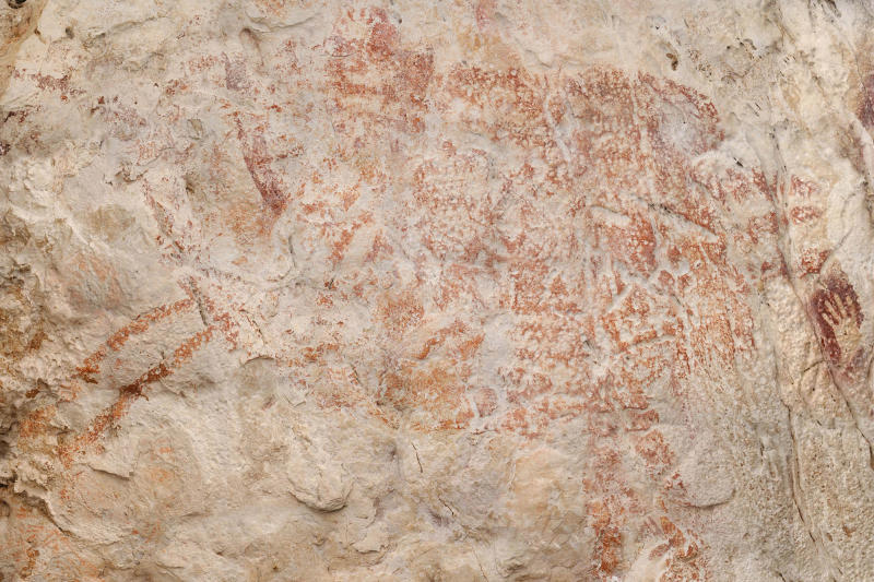 "This composite image from the book ""Borneo, Memory of the Caves"" shows the world's oldest figurative artwork dated to a minimum of 40,000 years, in a limestone cave in the Indonesian part of the island of Borneo. Scientists say the red silhouette of a bull-like beast, upper left, is the oldest known example of animal art. (Luc-Henri Fage/kalimanthrope.com via AP)"