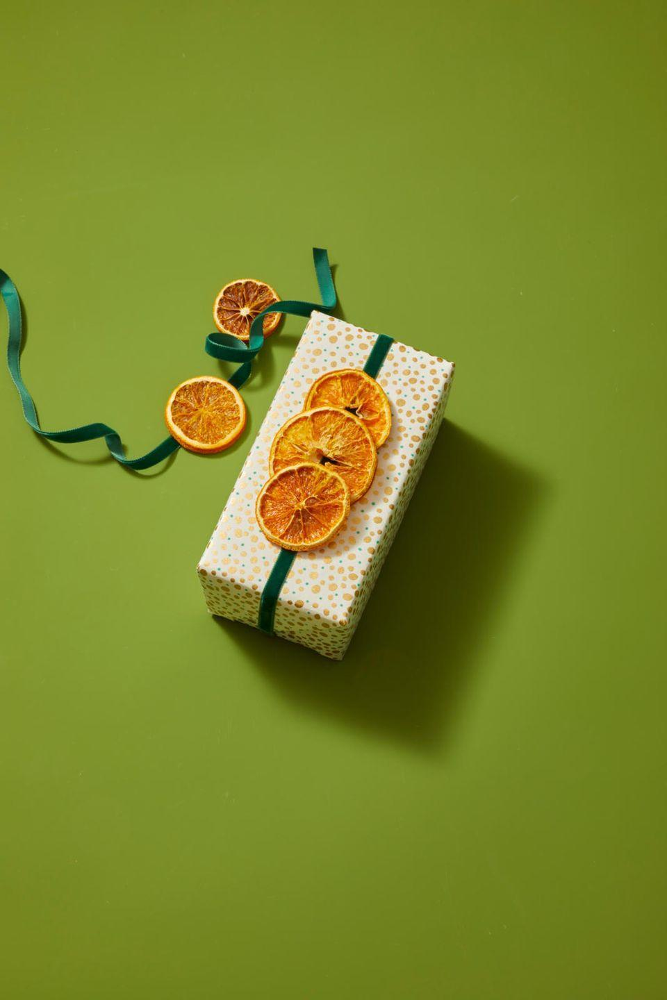 <p>Or, if you want an alternative to the woodland scene, string some dehydrated oranges onto a ribbon for a gift topper that looks like it came straight out of <em>Little Women</em>. Use the ribbon to hang the slices on a tree or garland afterward.</p>
