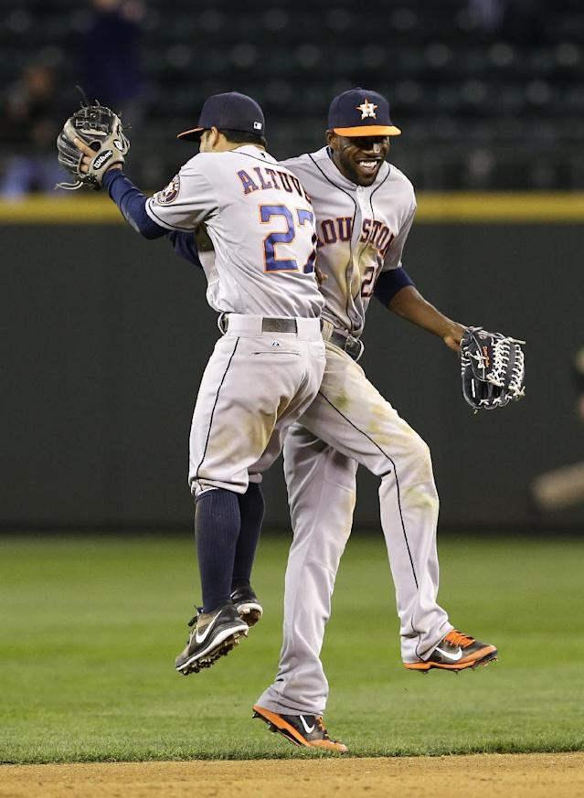 Houston Astros' Jose Altuve, left, leaps to bump shoulders with Astros' Dexter Fowler, after the Astros beat the Seattle Mariners 7-2 in a baseball game Monday, April 21, 2014, in Seattle. (AP Photo/Ted S. Warren)