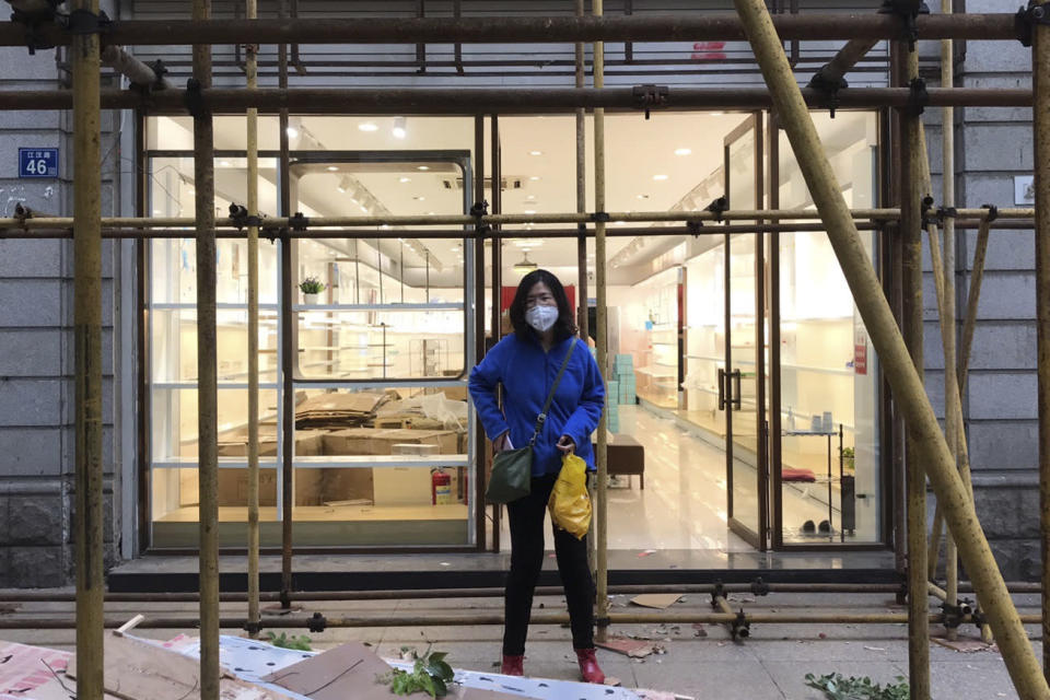 "In this photo taken April 11, 2020 and released by Melanie Wang, Zhang Zhan stand near scaffoldings outside a shop during a visit to Wuhan in central China's Hubei province. A Chinese court on Monday sentenced the former lawyer who reported on the early stage of the coronavirus outbreak to four years in prison on charges of ""picking fights and provoking trouble,"" one of her lawyers said. (Melanie Wang via AP)"