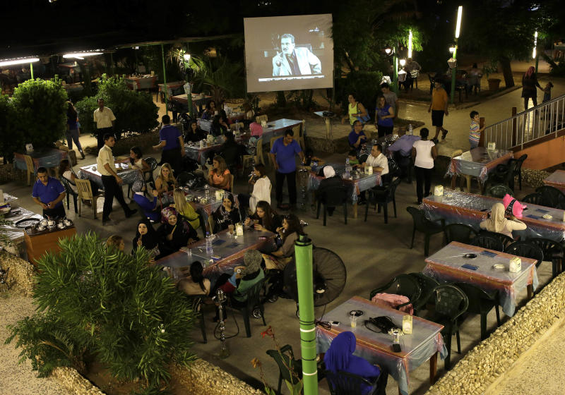 In this picture taken on Wednesday July 24, 2013, Lebanese and Syrian citizens gather at an outdoor coffee shop, as one of the Syrian popular series Al-Wiladah Men Al-Khasira (Birth from the Waist), is broadcast on a giant screen, in Beirut, Lebanon. Birth from the Waist is one of several Syrian soap operas airing during the Muslim holy month of Ramadan this year, almost all of them dealing with the Syrian civil war, now in its third year, spotlighting a conflict in which more than 100,000 people have been killed and millions of others uprooted from their homes. The series have captivated millions of viewers across the Arab world. (AP Photo/Hussein Malla)