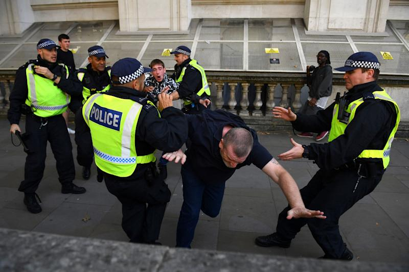 Police officers remonstrate with demonstrators on Parliament Square