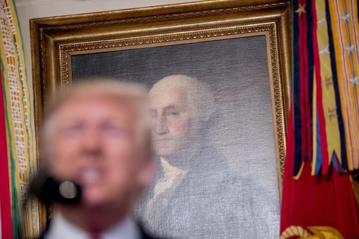 A painting of President George Washington is visible behind President Donald Trump, foreground, as he speaks in the Diplomatic Room of the White House in Washington, Sunday, Oct. 27, 2019, to announce that Islamic State leader Abu Bakr al-Baghdadi has been killed during a US raid in Syria. (AP Photo/Andrew Harnik)