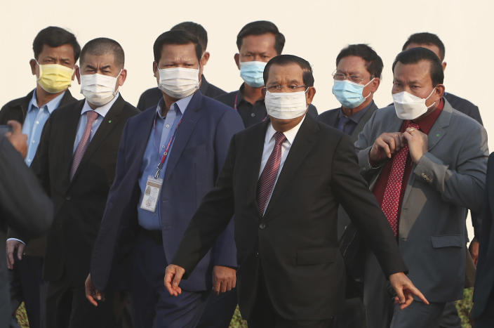 """Cambodian Prime Minister Hun Sen, third right, arrives for a handing over ceremony at Phnom Penh International Airport, in Phnom Penh, Cambodia, Sunday, Feb. 7, 2021. Cambodia on Sunday received its first shipment of COVID-19 vaccine, a donation of 600,000 doses from China, the country's biggest ally. Beijing has been making such donations to several Southeast Asian and African nations in what has been dubbed """"vaccine diplomacy,"""" aimed especially at poorer countries like Cambodia. (AP Photo/Heng Sinith)"""