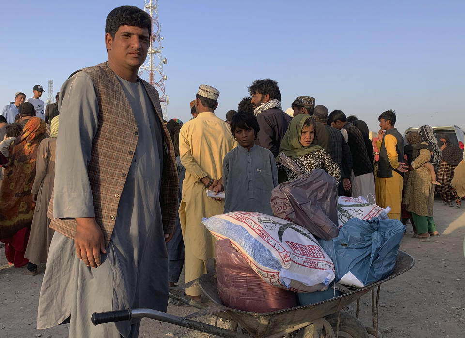 An Afghan man prepares to push a wheelbarrow with items of food distributing by an Islamabad-based Christian organization on the outskirts of Chaman, a border town in the Pakistan's southwestern Baluchistan province, Tuesday, August 31, 2021. Dozens of Afghan families have crossed into Pakistan through the southwestern Chaman border a day after the U.S. wrapped up its 20-year military presence in the Taliban-controlled country. (AP Photo)