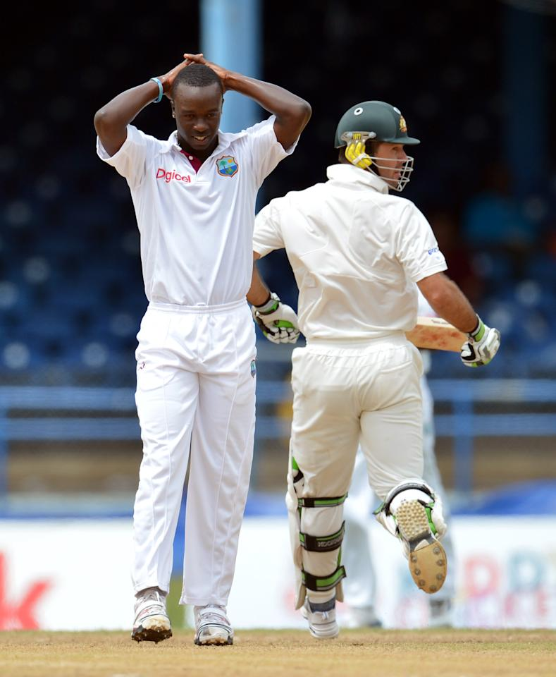 West Indies bowler Kemar Roach (L) reacts to a hit by Australian batsman Ricky Ponting (R) during the final day of the second-of-three Test matches between Australia and West Indies April 19, 2012 at Queen's Park Oval in Port of Spain, Trinidad.