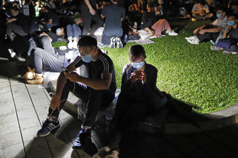 FILE - In this Wednesday, June 12, 2019, file photo, extradition law protesters browse their smartphones near the Legislative Council in Hong Kong. The Hong Kong-based web forum LIHKG and Telegram, the encrypted messaging app, have served as crucial organizing platforms for the largely leaderless protests (AP Photo/Kin Cheung, File)