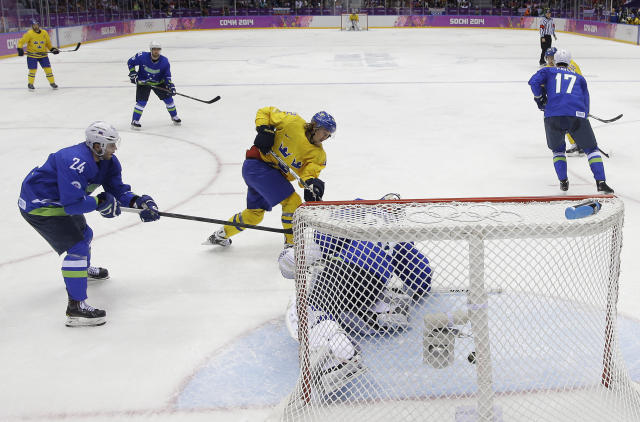 Sweden forward Carl Hagelin, center, shoots and scores against Slovenia goaltender Robert Kristan in the third period of a men's ice hockey game at the 2014 Winter Olympics, Wednesday, Feb. 19, 2014, in Sochi, Russia. (AP Photo/Mark Humphrey)