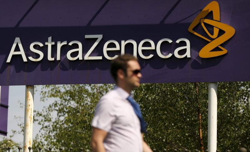 A man walks past a sign at an AstraZeneca site in Macclesfield