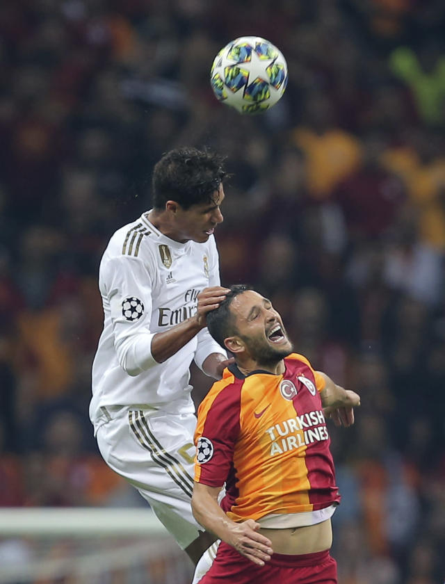 Real Madrid's Raphael Varane, left, jumps for the ball with Galatasaray's Florin Andone during the Champions League group A soccer match between Galatasaray and Real Madrid in Istanbul, Tuesday, Oct. 22, 2019. (AP Photo)