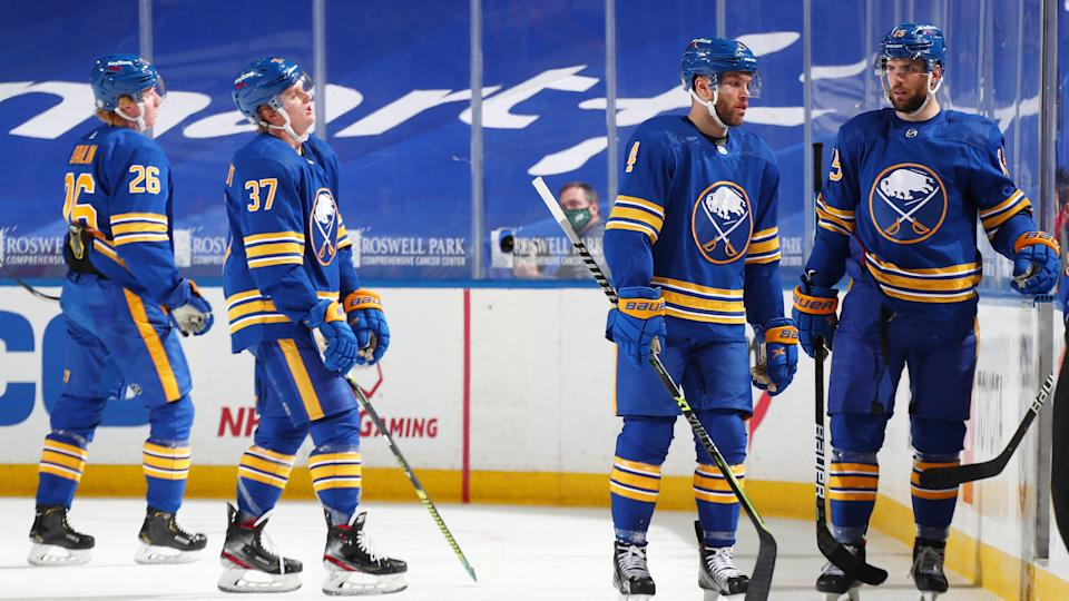 BUFFALO, NY - MARCH 29: Rasmus Dahlin #26, Casey Mittelstadt #37, Taylor Hall #4 and Riley Sheahan #15 of the Buffalo Sabres react to the overtime loss after an NHL game against the Philadelphia Flyers on March 29, 2021 at KeyBank Center in Buffalo, New York. Flyers won in overtime, 4-3. (Photo by Bill Wippert/NHLI via Getty Images)