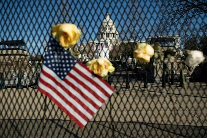 Roses and an American flag placed on the barrier erected to protect the US Capitol after a police officer died during the violence of January 6, 2021