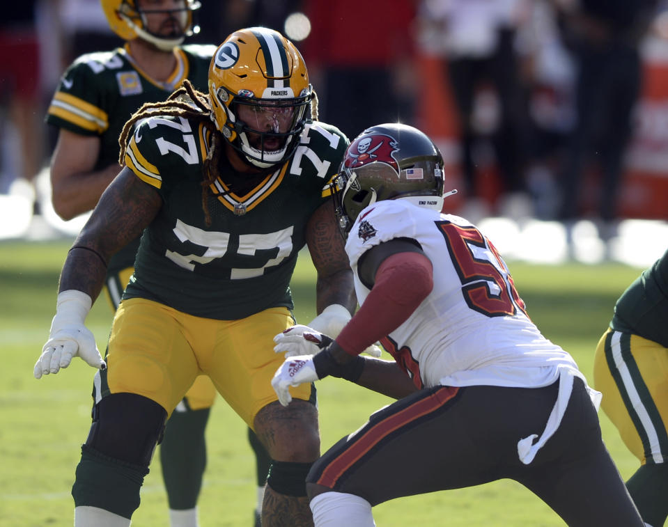 FILE - In this Oct. 18, 2020, file photo, Green Bay Packers offensive tackle Billy Turner (77) looks to block Tampa Bay Buccaneers outside linebacker Shaquil Barrett (58) during the first half of an NFL football game in Tampa, Fla. Green Bay's offensive line lost two of its original five starters to season-ending knee injuries, with right guard Lane Taylor going down in the opener. They were missing All-Pro center Corey Linsley for three games at midseason. Now they're continuing their Super Bowl chase without Bakhtiari. Yet the line hasn't missed a beat while helping make the Packers the NFL's highest-scoring team.(AP Photo/Jason Behnken, File)