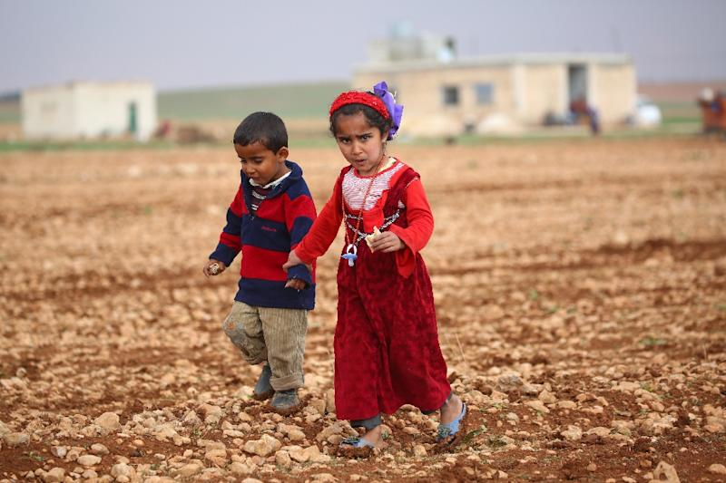 Syrian children displaced by clashes between regime forces and the Islamic State (IS) group walk in a field in Kharufiyah, 18 kilometres south of Manbij, on March 4, 2017 (AFP Photo/DELIL SOULEIMAN)