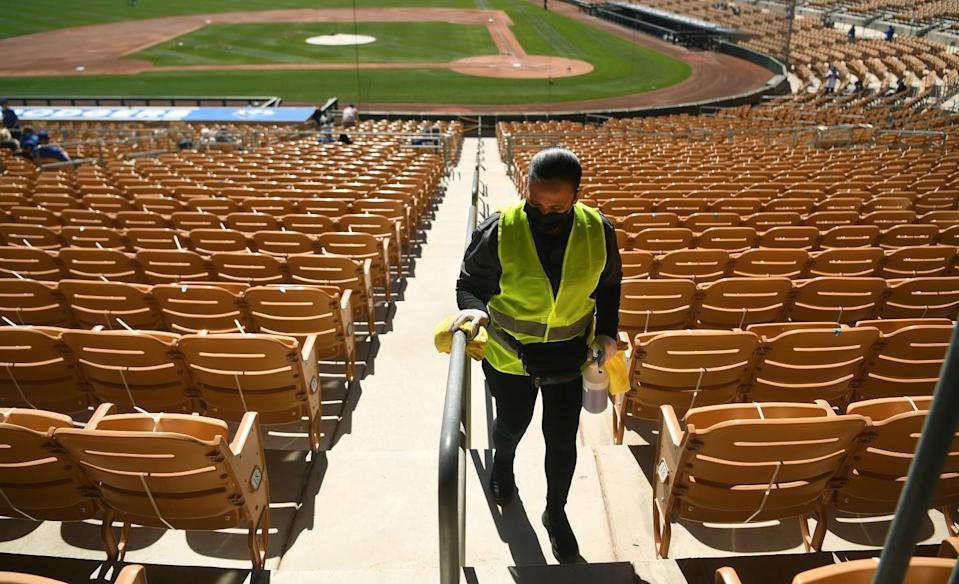 A worker wipes down a railing with disinfectant