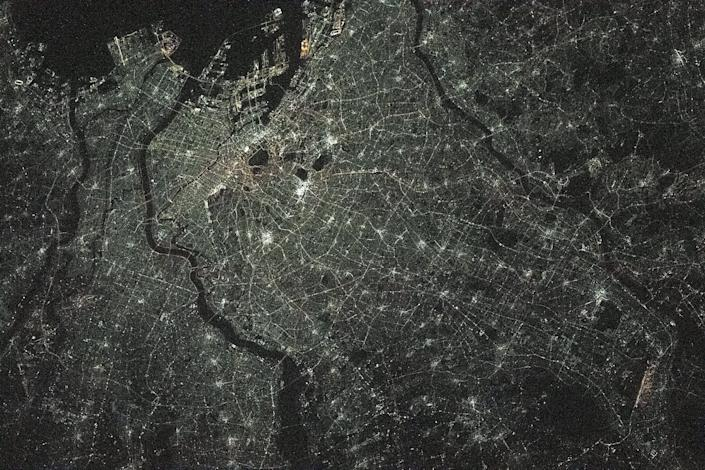tokyo city grid lit up green at night with thin dark rivers splitting the city as seen from above