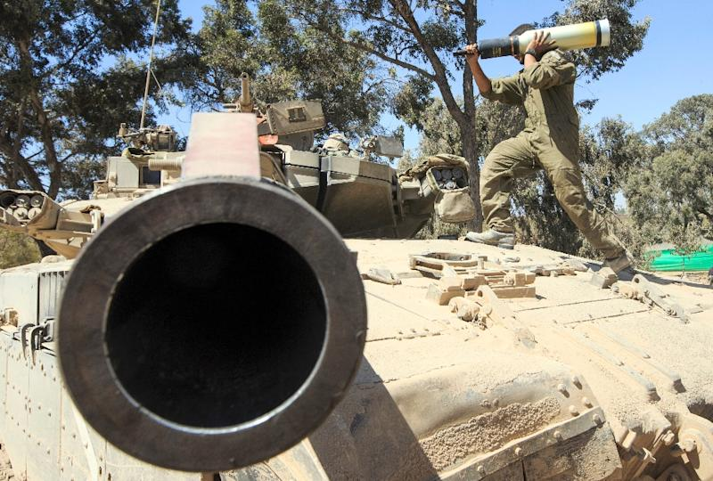 An Israeli soldier carries a shell as he and his comrades prepare their Merkava tanks stationed on the border between Israel and the Gaza Strip on July 31, 2014