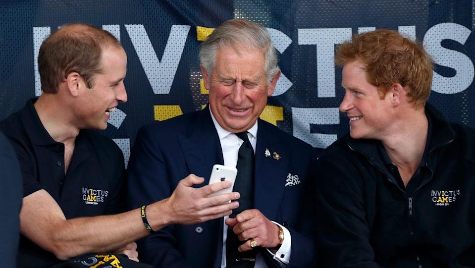 Prince William laughs as he shows Prince Charles something on his phone while Prince Harry looks on